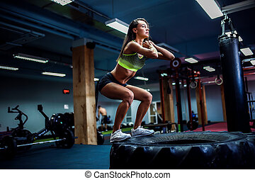 Fit young woman box jumping at a crossfit style.