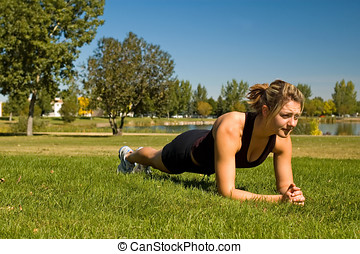 """Plank - Fit young woman doing the \\\""""Plank\\\"""" exercise."""