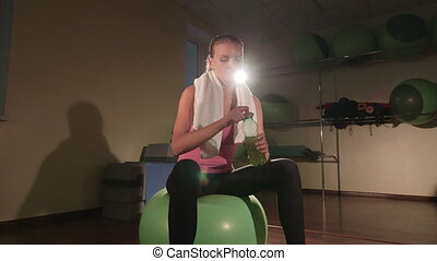 Fit young woman drinking energy drink from bottle after exercise in gym