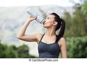 Fit young woman drinking water after workout