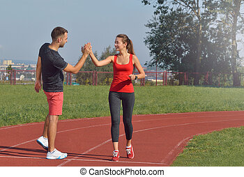 Fit young woman giving high five to her boyfriend after a run.