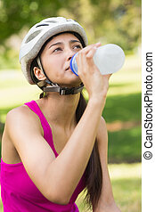 Fit young woman in helmet drinking