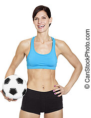 Fit smiling young woman in sports clothing with a soccer ball on white background