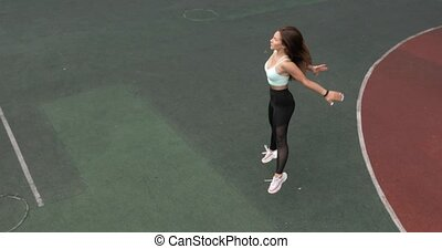 Fit young woman is training doing squats and jumps on stadium in College campus.