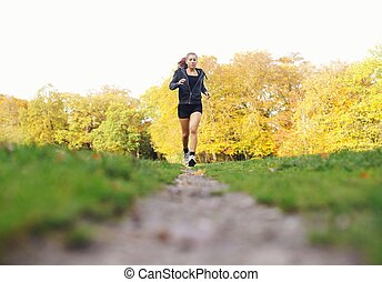 Fit young woman jogging in a park on a summer day