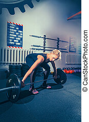 Fit young woman lifting barbell working out in a gym