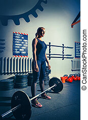 Fit young woman lifting barbells working out in a gym