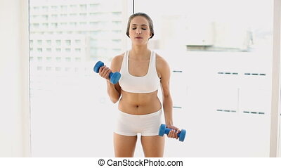 Fit young woman lifting dumbbells