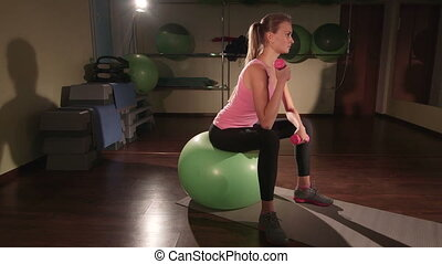 Fit young woman lifting light dumbbell on fitness ball in gym
