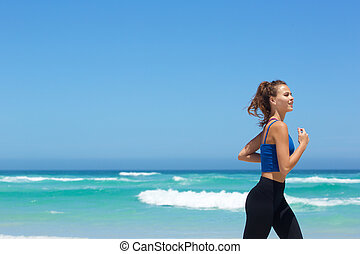 Fit young woman running by the sea
