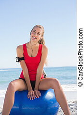 Fit young woman sitting on exercise ball
