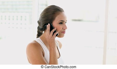 Fit young woman talking on the phone at home in a bright...