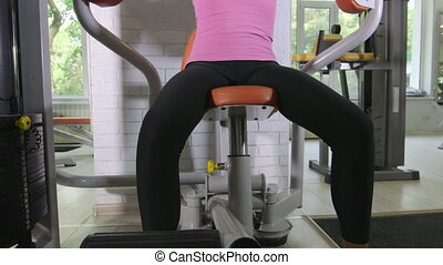 Fit young woman training on weight exercise machine at fitness health club