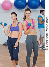 Fit young women holding dumbbells with a man in background