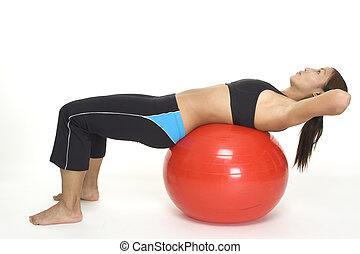 A female fitness instructor demonstrates the starting position of the fitball crunch