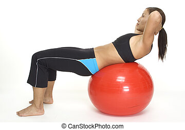 A female fitness instructor demonstrates the finishing position of the fitball crunch