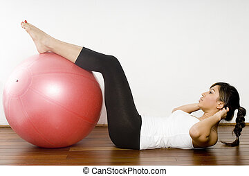 Fitball Exercise - A young attractive asian woman doing a ...