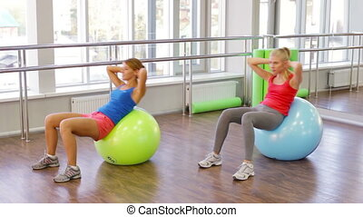 Fitball Workout - Determined athletes doing abdominal...