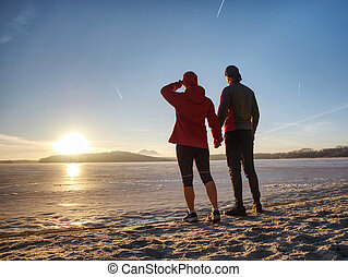Fitnes couple man and woman. Winter landscape with sun