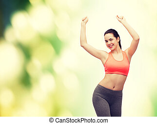 smiling teenage girl in sportswear dancing - fitness and ...