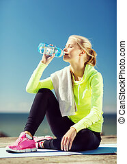 woman drinking water after doing sports outdoors - fitness...