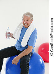 fitness and yoga - senior adult sitting on fitness ball in...