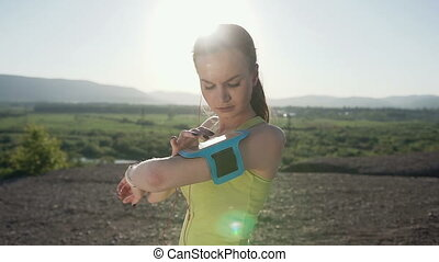 Fitness athlete girl running fast with speed wearing phone armband showing with smartphone touch screen on the mountain at sunset. Runner listening to music. Cardio workout