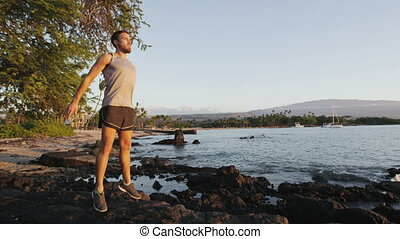 Fitness athlete man doing jump squat jumping outside in nature landscape. Jump squats plyometrics exercise strength training by fit male model working out exercising outdoors on beach in summer.