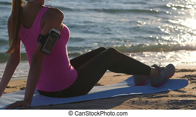 Fitness athletic girl relaxing after exercise on the beach at sunset