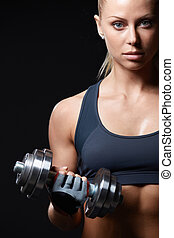 Athletic girl with dumbbells on a dark background