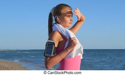Fitness athletic girl with wireless headset and smart phone on the beach