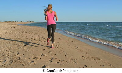 Fitness athletic woman jogging along the beach