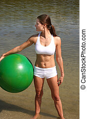 Fitness - Attractive woman on beach working out with a...
