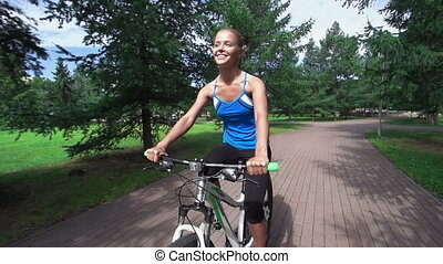 Fitness Awareness - Slow motion of smiley pretty girl riding...
