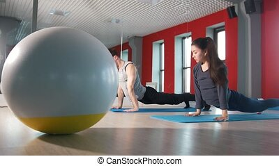 Fitness ball in front of athletic man and woman trains in the fitness room