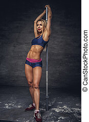 Fitness blond female with barbell grif.