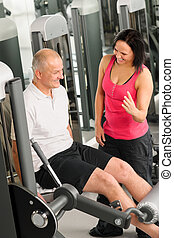 Fitness center active man exercising with trainer