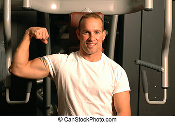 fitness center man - strong man flexing muscles in gym