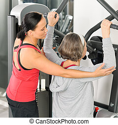Fitness center trainer senior woman exercise back