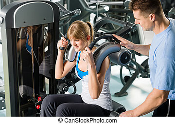 Fitness center young woman exercise with trainer - Fitness...