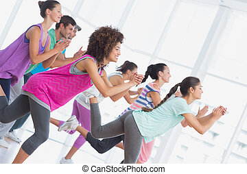 Fitness class and instructor doing pilates exercise in a ...