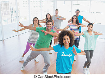 Fitness class and instructor doing pilates exercise in a...