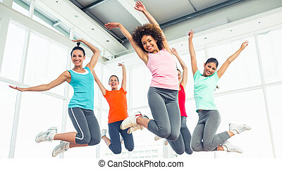 Fitness class and instructor jumpin