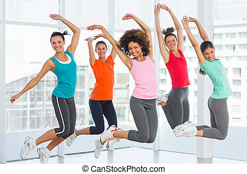 Fitness class and instructor jumping in fitness studio -...