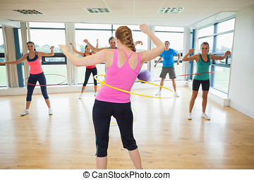 Fitness class and instructor swinging hula hoops at the ...