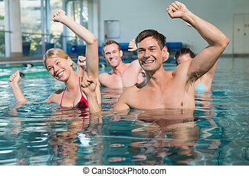 Fitness class doing aqua aerobics in swimming pool at the...