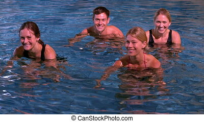 Fitness class doing aqua aerobics in the pool smiling at...