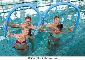 Fitness class doing aqua aerobics with foam rollers