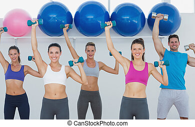 Fitness class exercising with dumbbells in gym