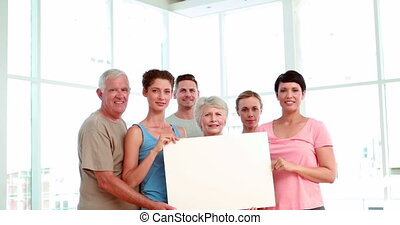Fitness class holding a white poster an cheering at the gym